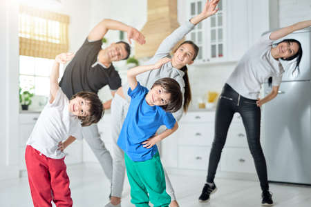 Its warming up. Happy latin family exercising, having morning workout together at home