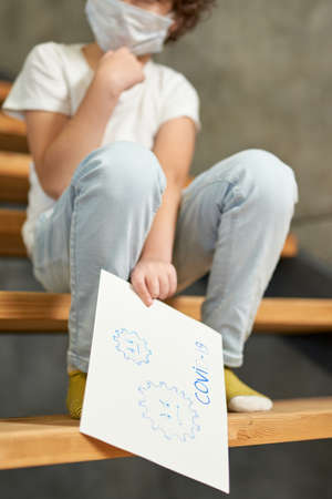 Cropped shot of little boy sitting on the stairs, holding Covid-19 drawing during remote studying at home