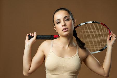 Beautiful female tennis player posing in studio