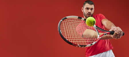Website header of Seriously strong athlete male in red shirt playing tennis isolated on red background