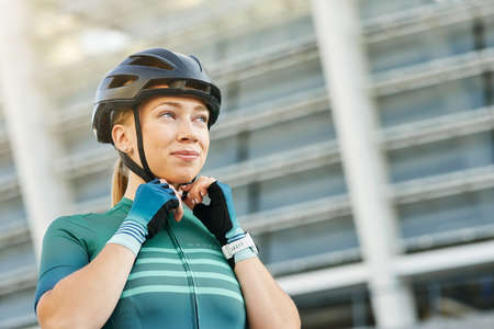 Portrait of young woman, female cyclist looking away and fastening her cycling helmet while posing outdoors on a daytime