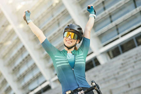 Portrait of successful professional female cyclist in cycling garment raised her arms, smiling at camera while standing with her bike outdoors on a daytime Imagens