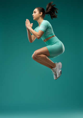 Charming young woman in sportswear jumping in the air Banco de Imagens