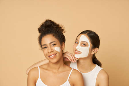 Studio shot of two young women, female friends having fun, smiling at camera while posing with facial masks on isolated over beige background Archivio Fotografico
