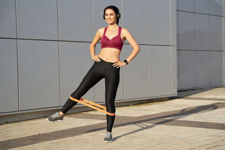 Smiling sportswoman in wireless headphones doing exercises