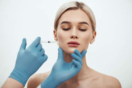 Botox injection. Young attractive woman keeping her eyes closed while doctors hand making an injection in her face. Studio shot Stockfoto