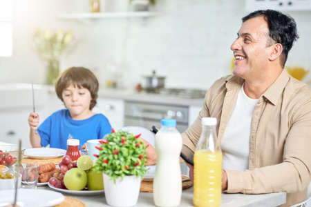 Cheerful middle aged hispanic man smiling, while having breakfast with his family, sitting at the kitchen table near his son at home