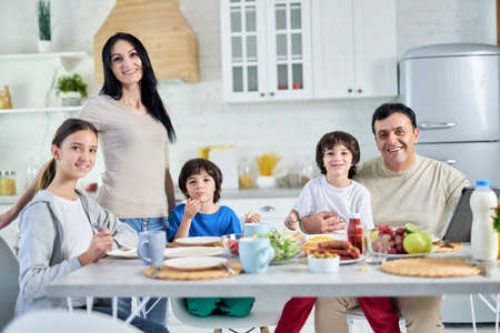 Eating together. Smiling hispanic parents spending time with their little children, having breakfast together at home Foto de archivo