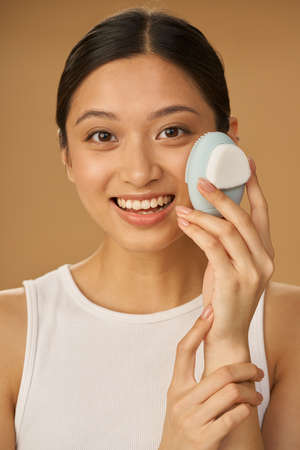 Excited young woman smiling at camera while using silicone facial cleansing brush, posing isolated over beige background