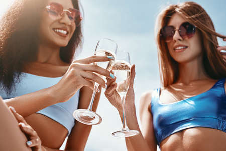 Unforgettable…That's what holidays meant to be. Portrait of attractive girls sitting by the pool, having fun