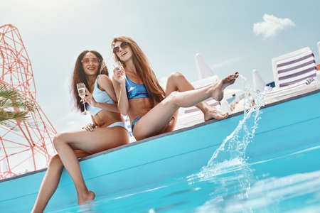 Home is where the pool is. Girls sitting by the pool, splashing the water and laughing