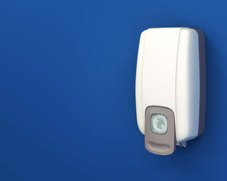 sanitizing: Hand sanitizer dispenser on blue wall with layout copy space and clipping path. Stock Photo