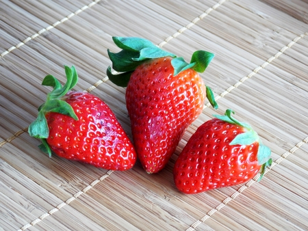 Photo of three big red strawberries on kitchen placemats photo