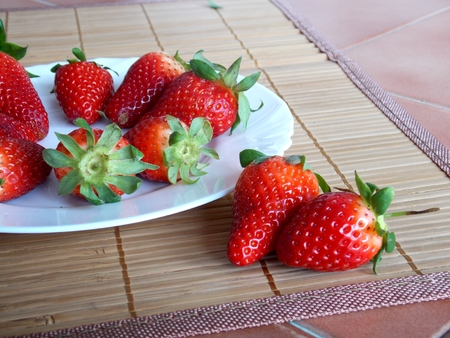 Photo of big red strawberries on plate and kitchen desk photo