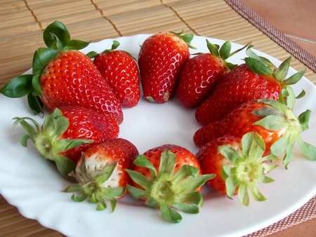 Photo of big red strawberries on white plate photo