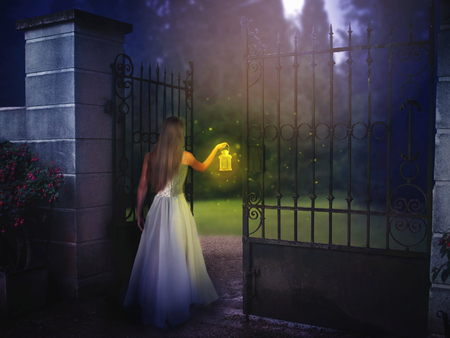 Young woman standing by the gate in night with lantern