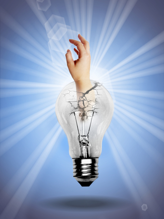 White light bulb on blue background with human hand