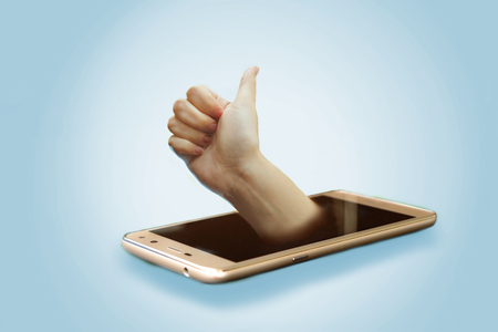 Human hand with gesture good choice from mobile phone Stock Photo