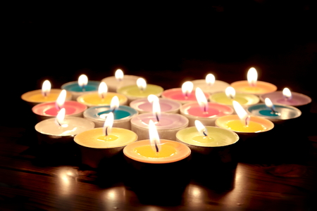 Shining colorful candles in night time in shape of heart