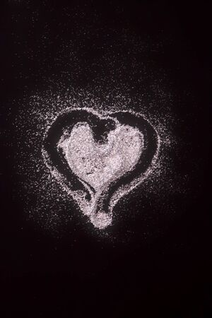 Black background decorated with heart of silver glitter