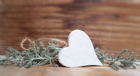 Photo of white heart on wooden background and plant decoration