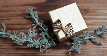 Photo of golden gift on wooden background with plant