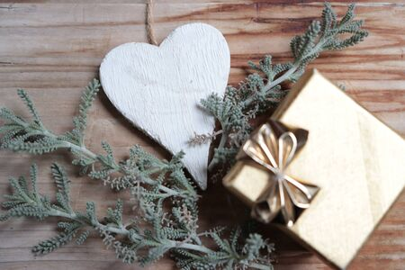 Photo of golden gift with white heart on wooden background and plant