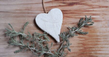 Photo of white heart on wooden background with plant