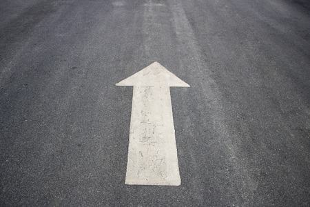 frayed: Drawing a frayed white arrow on the asphalt Stock Photo