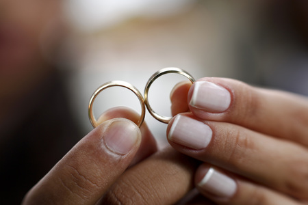 Two hands holding two gold rings wedding