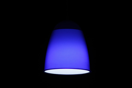 Blue circular lamp on black background