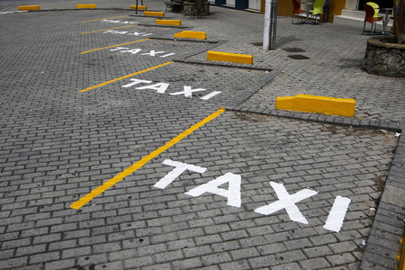 Taxi sign posted in public way with white paint Stok Fotoğraf