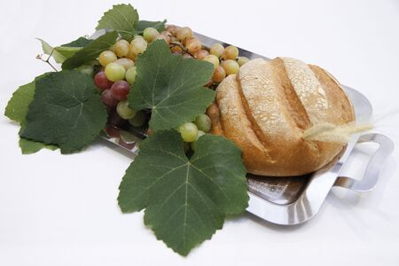 Traditional bread, grapes with leaves on metal tray for offertory at Catholic Mass