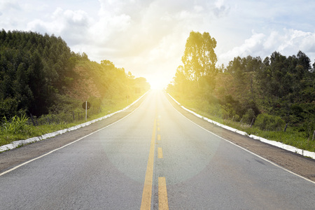 Asphalt road with straight uphill with sunlight
