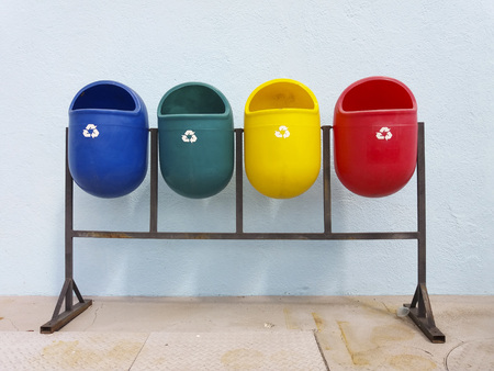 Colored public bins in the sunlight and outdoor separate for paper, glass, metal and plastic collection