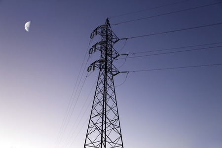 Electricity transmission tower silhouetted against blue sky at dusk and moon
