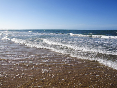 View of water surface of sea or ocean with horizon and blue sky or low waves - Canoa Quebrada in the city of Aracati, Fortaleza, Ceara, Brazil