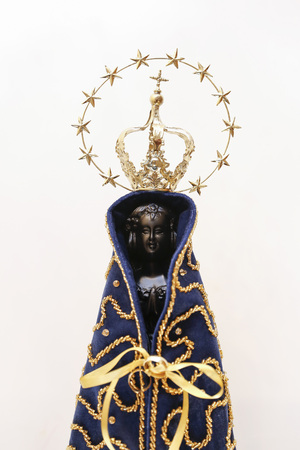 Statue of the image of Our Lady of Aparecida, mother of God in the Catholic religion, patroness of Brazil, isolated, with alliances, in a neutral background environment