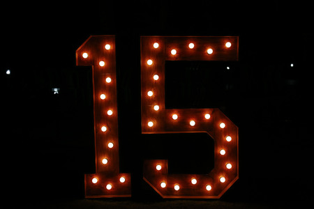 Number fifteen with lights on and clear - fifteen years - fifteen illuminated - large and clear number against dark background Stock Photo