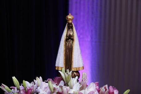 Statue of the image of Our Lady of Aparecida, mother of God in the Catholic religion, patroness of Brazil, decorated with flowers and white mantle