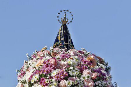 Standbeeld van het beeld van Onze Lieve Vrouw van Aparecida, moeder van God in de katholieke religie, patrones van Brazilië, versierd met bloemen Stockfoto