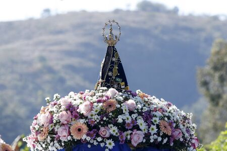Statue of the image of Our Lady of Aparecida, mother of God in the Catholic religion, patroness of Brazil, decorated with flowers
