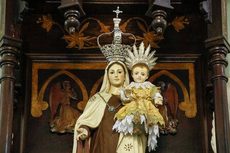 Statue of the image of Our Lady of Carmel, Nossa Senhora do Carmo, mother of God in the Catholic religion, decorated with flowers Фото со стока