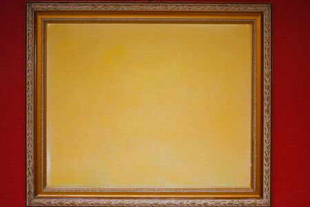 yellow frame with wood frame on red wall background - decorated environment