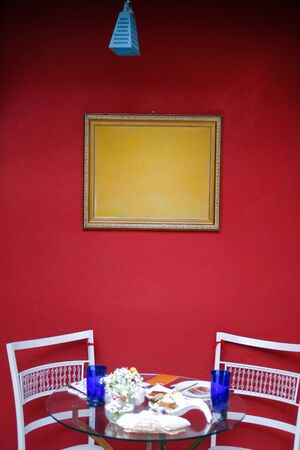 red walled environment, yellow wood-framed wall frame, chairs for throw, lunch and dinner Stockfoto
