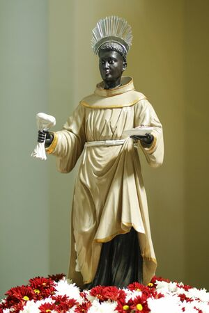 Statue with image of St. Benedict on altar decorated with flowers, OFM Cap, Order of Friars Minor Capuchin (Ordo Fratrum Minorum Capuccinorum)