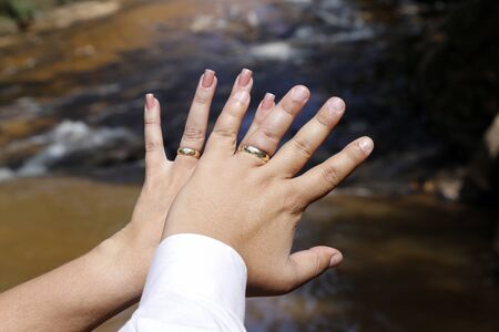 Grooms hands joined using wedding rings - golden wedding rings