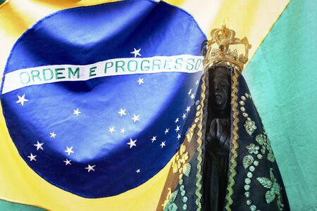 Statue of the image of Our Lady of Aparecida, mother of God in the Catholic religion, patroness of Brazil and Brazil flag