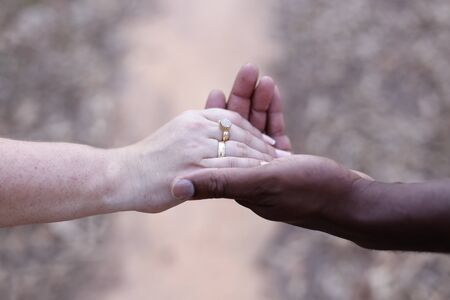 white hand and black hand united - Grooms hands joined using wedding rings - golden wedding rings