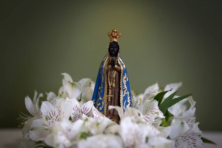 Statue of the image of Our Lady of Aparecida, mother of God in the Catholic religion, patroness of Brazil, decorated with flowers and orchids Imagens